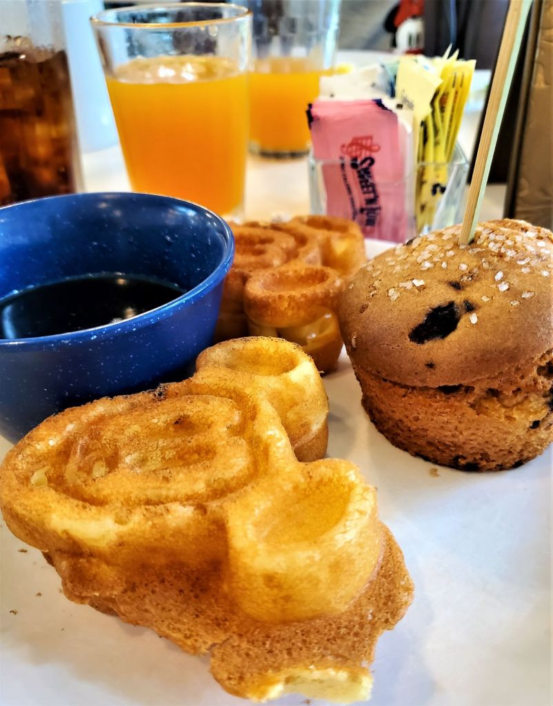 mickey waffles, syrup, and blueberry muffin
