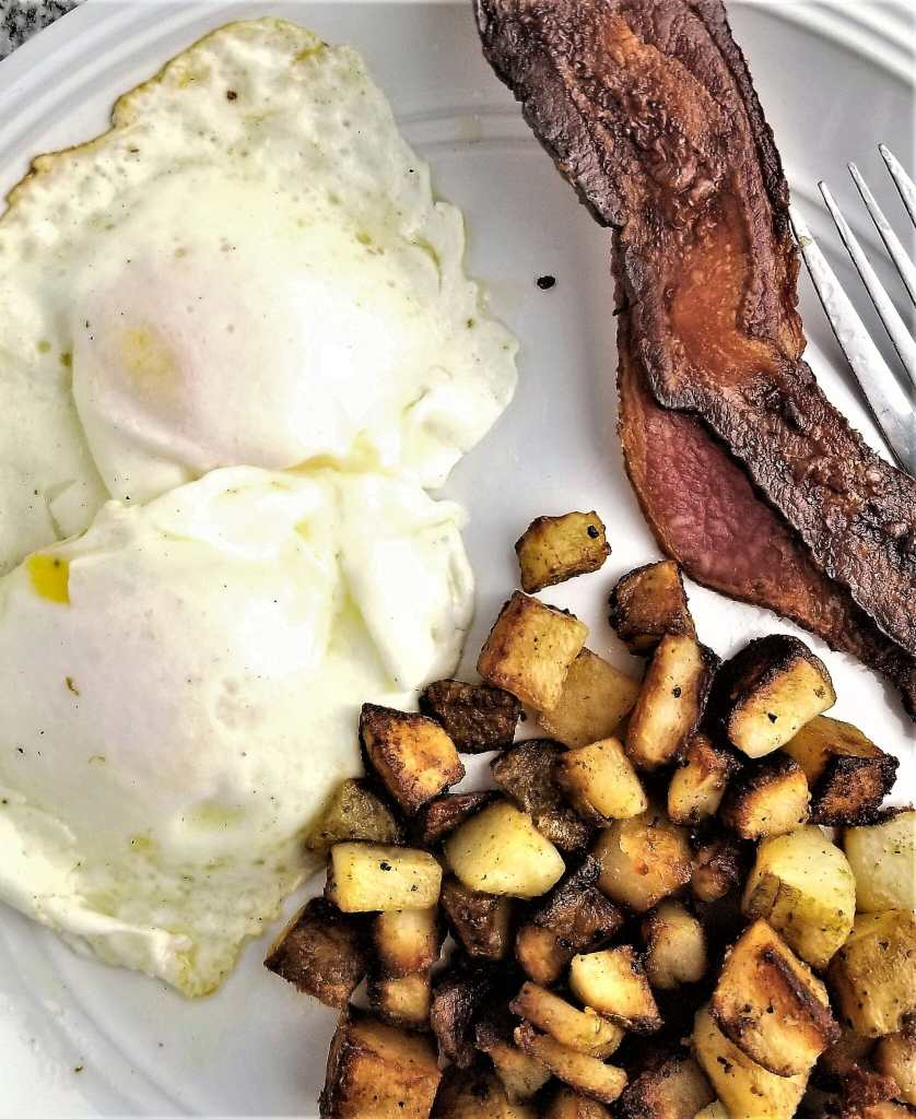 simple breakfast potatoes on a plate with eggs and bacon