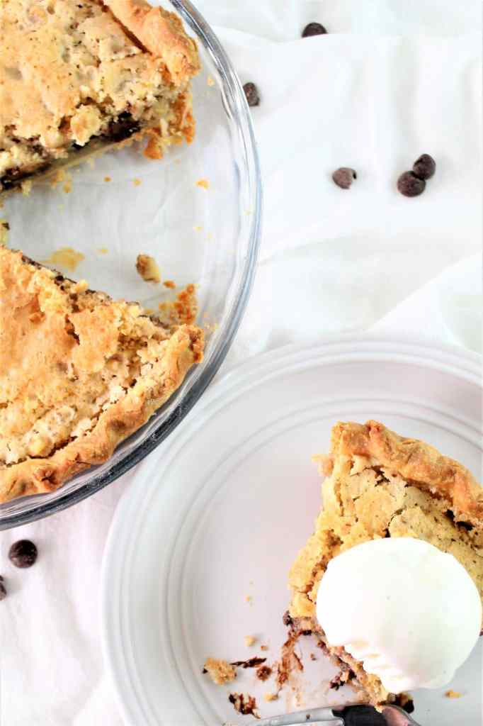 gluten free chocolate chip pie with one piece cut out and on a white plate