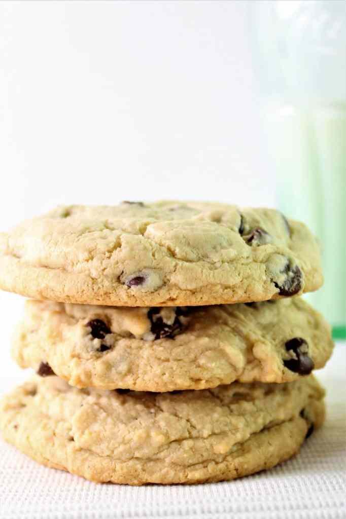 three stacked gluten free chocolate chip cookies with milk and straw