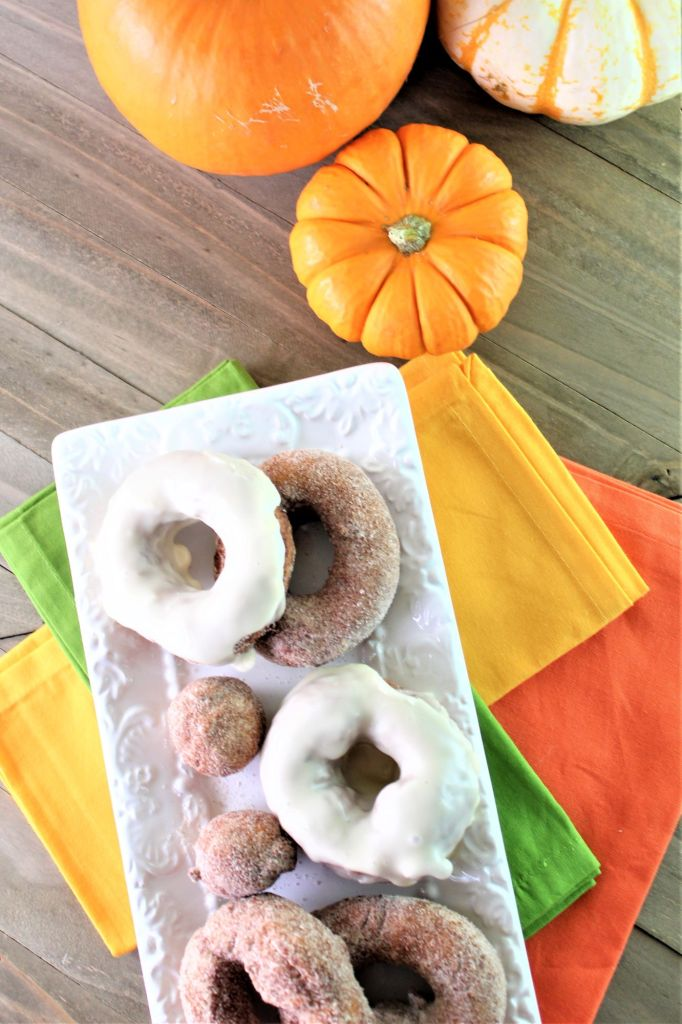 donuts on white tray over colorful napkins with pumpkins in the background