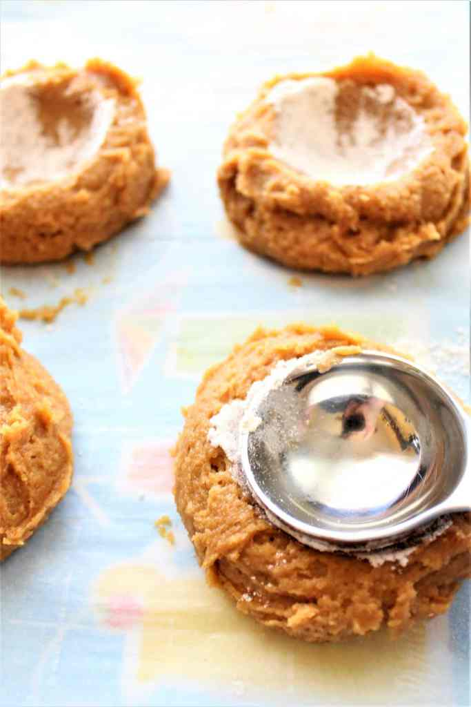 making well in center of cookies with spoon