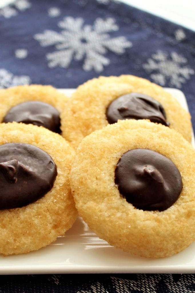 chocolate thumbprint cookies on white square plate with blue snowflake napkin