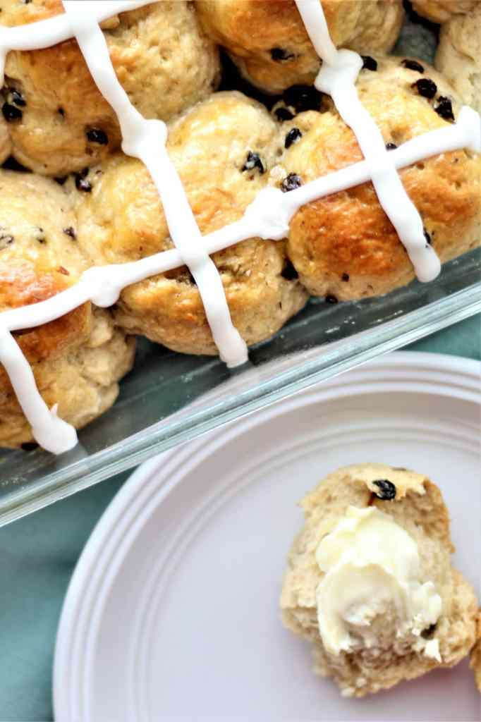 overhead shot of hot cross buns in pan with one on a white plate spread with butter