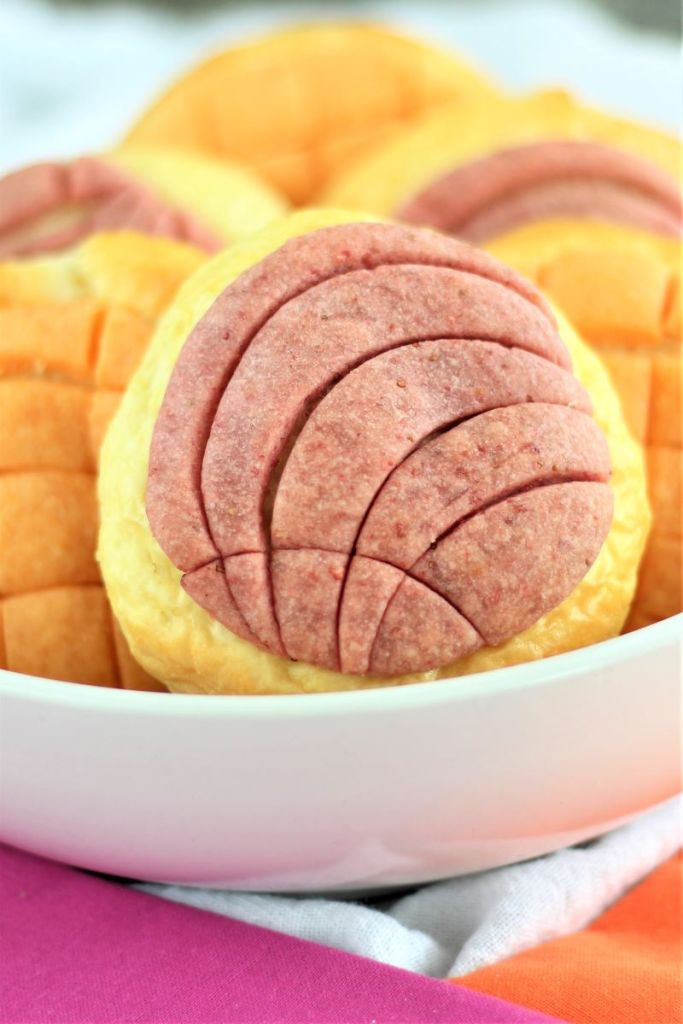 purple and orange shell and grid conchas in white bowl