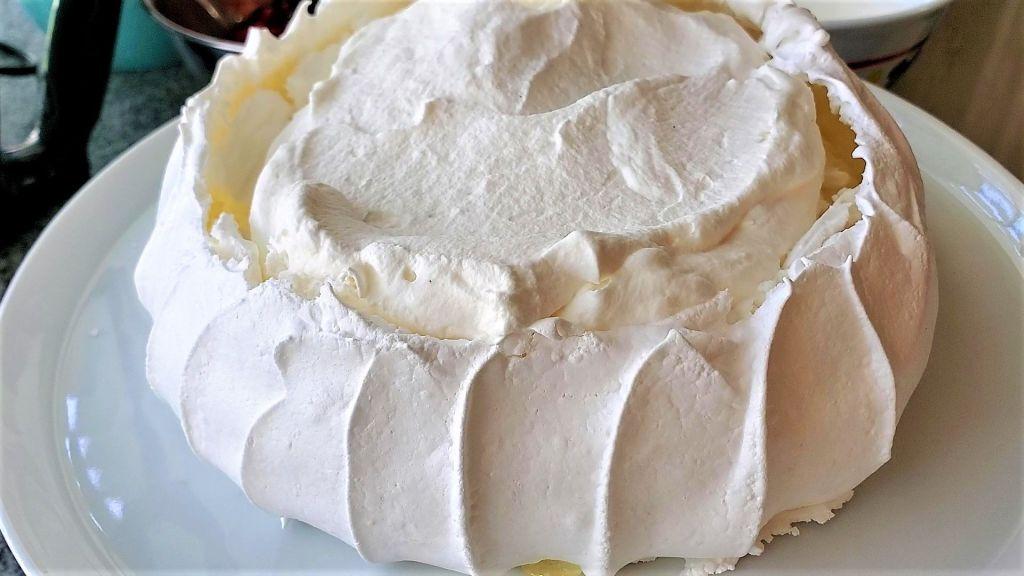 adding whipped cream to top of pavlova