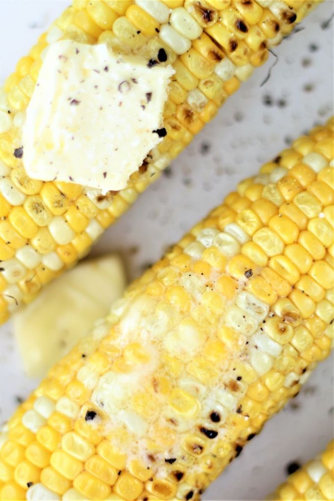 up close picture of two ears of corn with butter melted on top