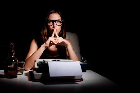 donna che pensa prima di scrivere alla macchina da scrivere