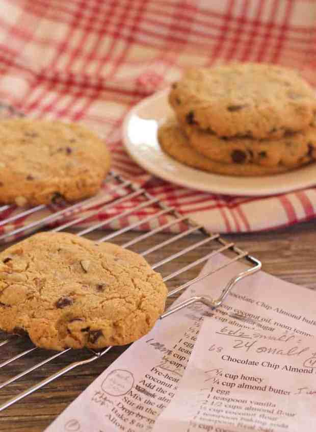Jumbo Chocolate Chip Almond Cookies on cooling rack and on plate, with marked up recipe drafts