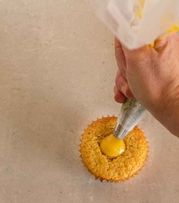 Piping lemon curd into Lemon Honey Chiffon Cupcakes