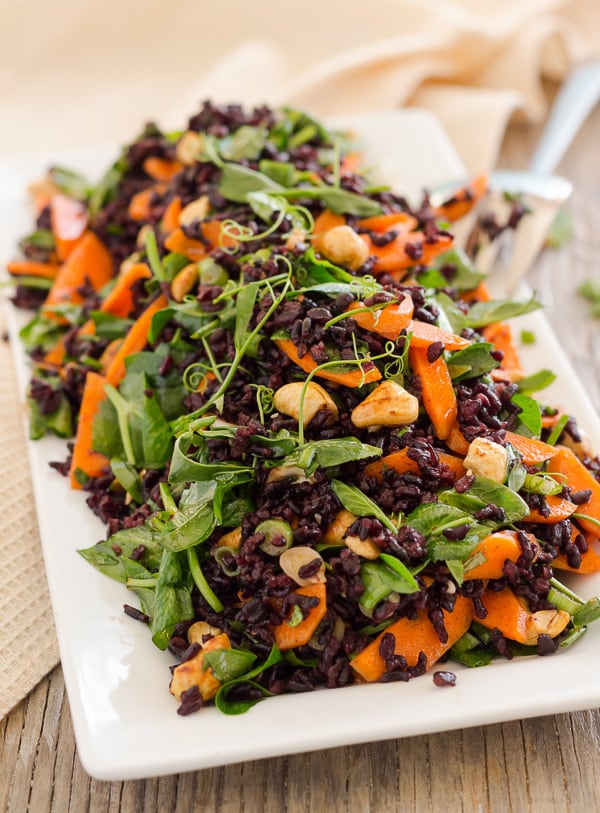 Vegan Black Rice and Pea Shoot salad with zesty lime, sesame, and tamari dressing. With tamari roasted cashews. Gluten free.