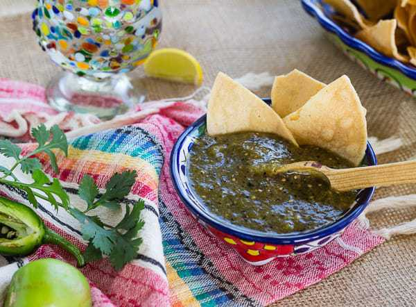 Homemade Roasted Green Tomatillo Salsa with tortilla chips and tequila snifter