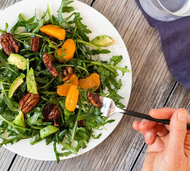 Arugula Salad with Clementines and Maple Pepper Pecans with hand and fork
