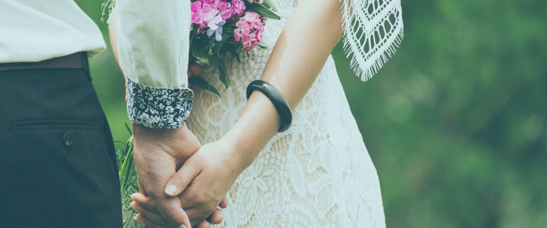 Een bruidspaar dat de handen vasthoud