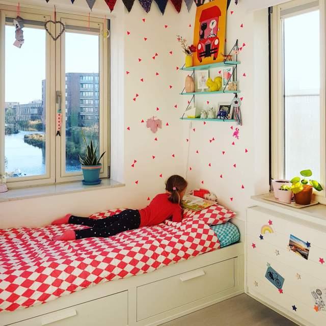 Binnenkijker: kleine witte kinderkamer met roze en geel, laag bed met lades er onder