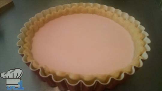 The custard is poured into the par-baked tart shell and left to cool and set before peach slice assembly.