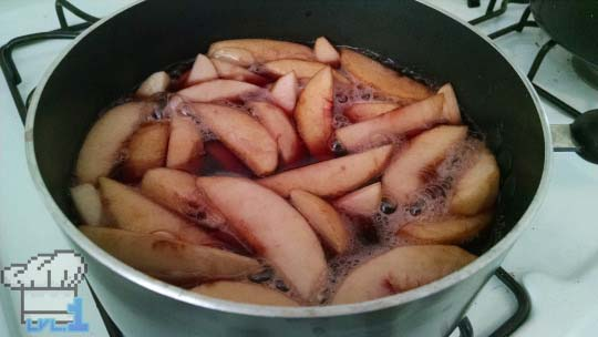 Sliced peaches being poached in liquid before assembling them into tart shell to be baked.
