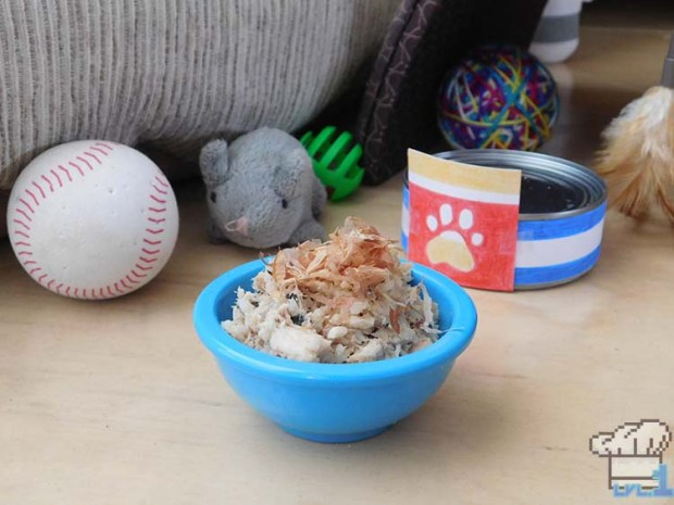 A bowl of the finished recipe of Bonito Bitz cat food, among an array of various cat toys.