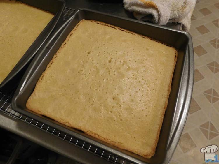 A pan of freshly baked almond genoise cake removed from the oven and cooling before slicing.
