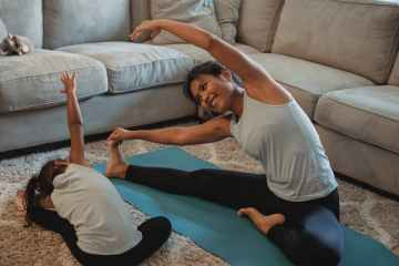 cheerful asian mother and daughter stretching body in living room
