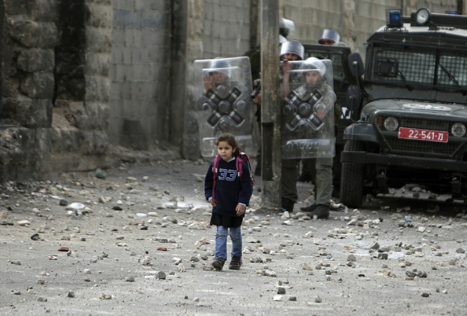 Ammar Awad/Reuters girl going to school in Palestine, with combat troops looking on