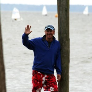 Coach Craig waving with sailboats in the background