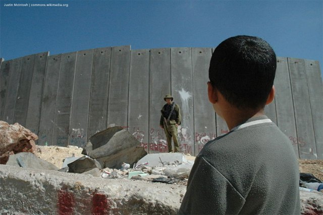A Palestinian boy and Israeli soldier in front of the Israeli West Bank Barrier.