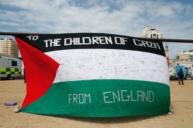 School children sign messages on the Palestinian flag in solidarity with the people in Gaza