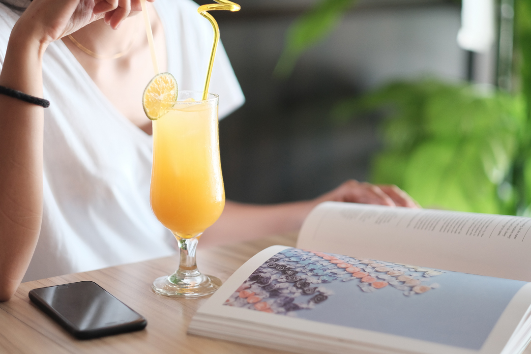 Young woman reading a book and drinking a juice