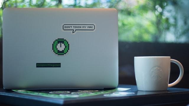 white mug beside laptop photo