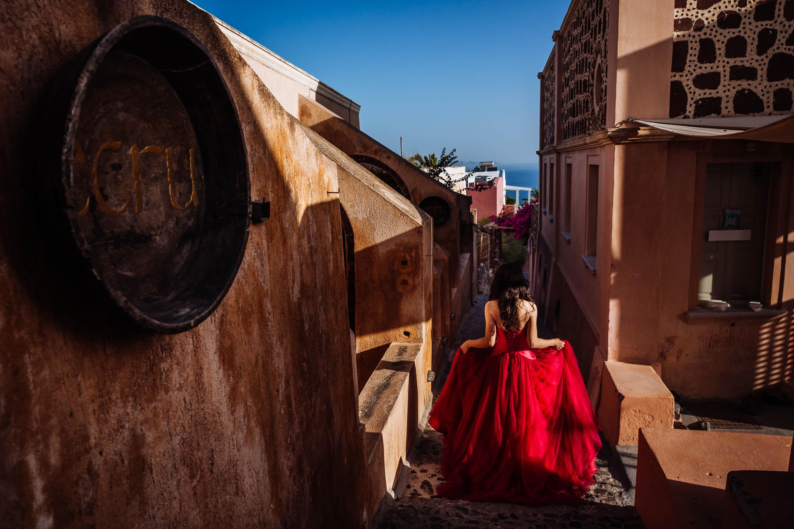 Bride in red dress walks outside