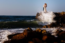 Couple standing on rocks, water splashes