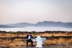 Far shot of bride and groom with water and mountains