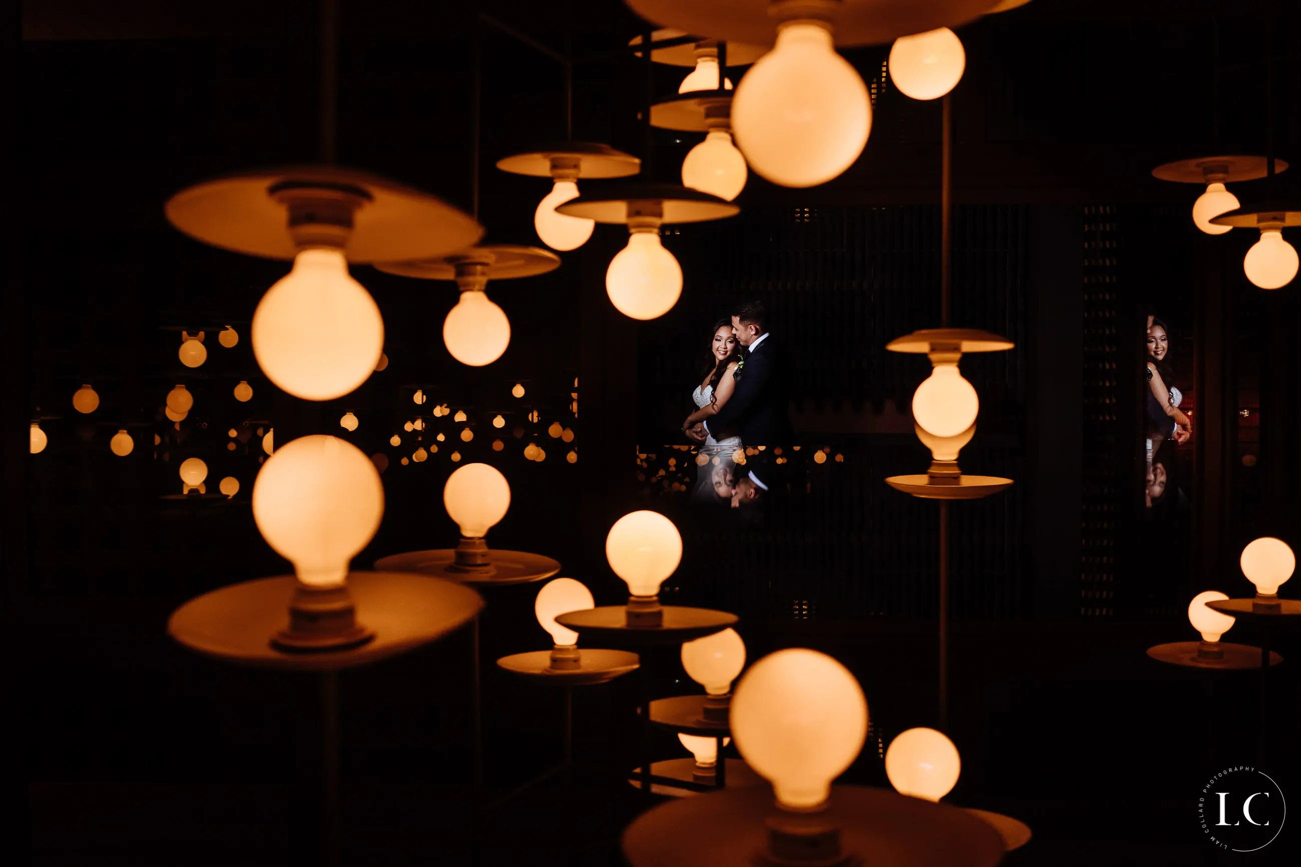 Various lightbulbs lit up with view of bride and groom