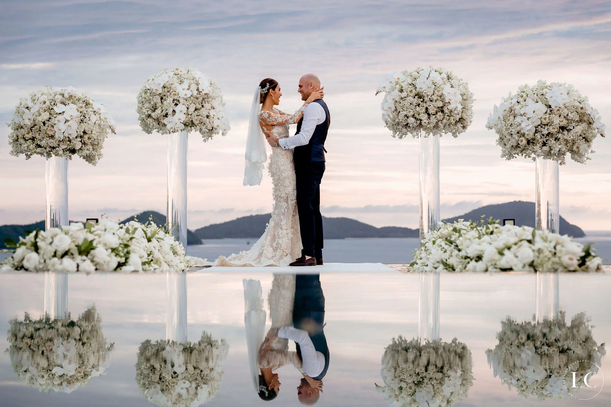 bride and groom embracing with water reflection