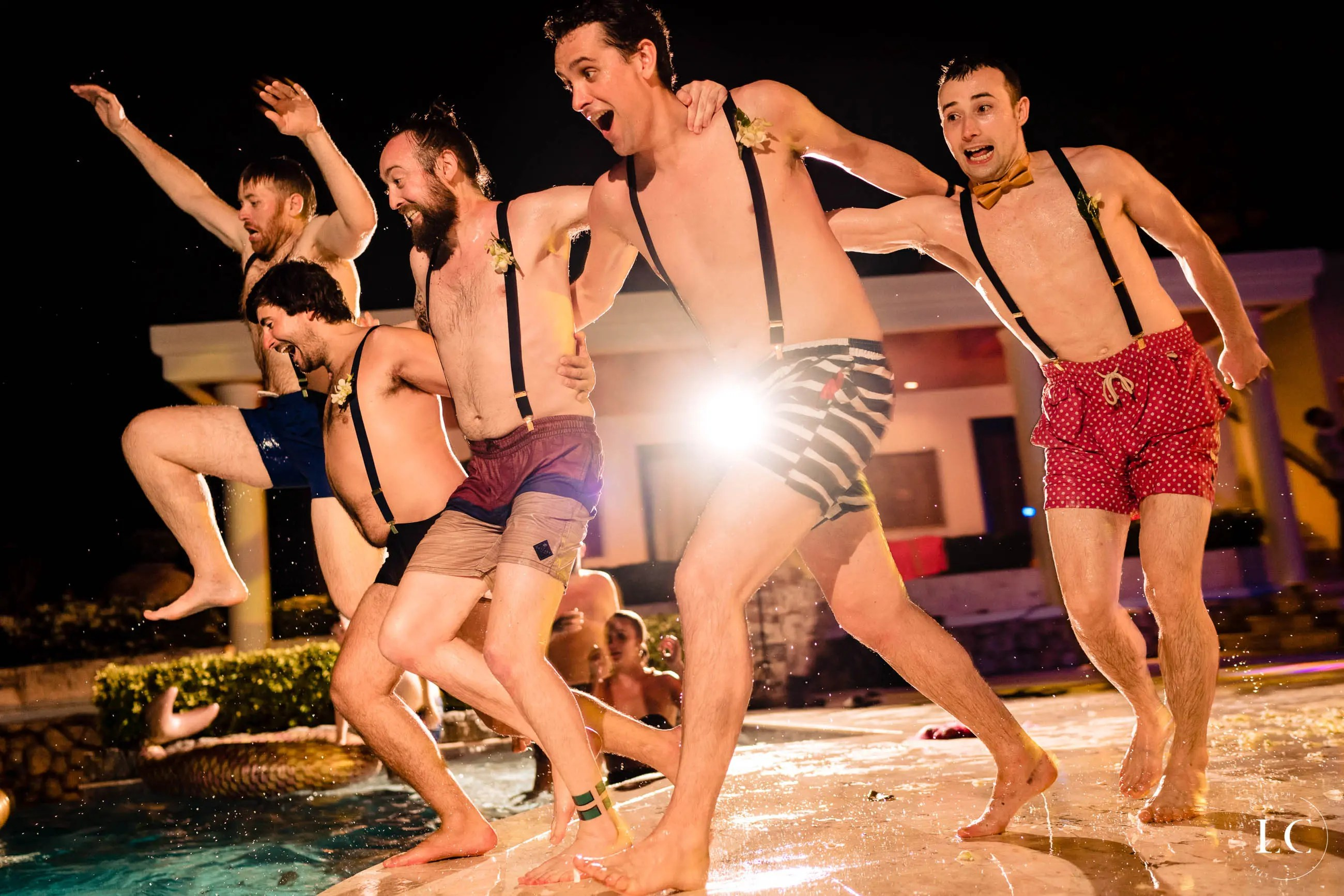 Groomsmen jumping into a pool