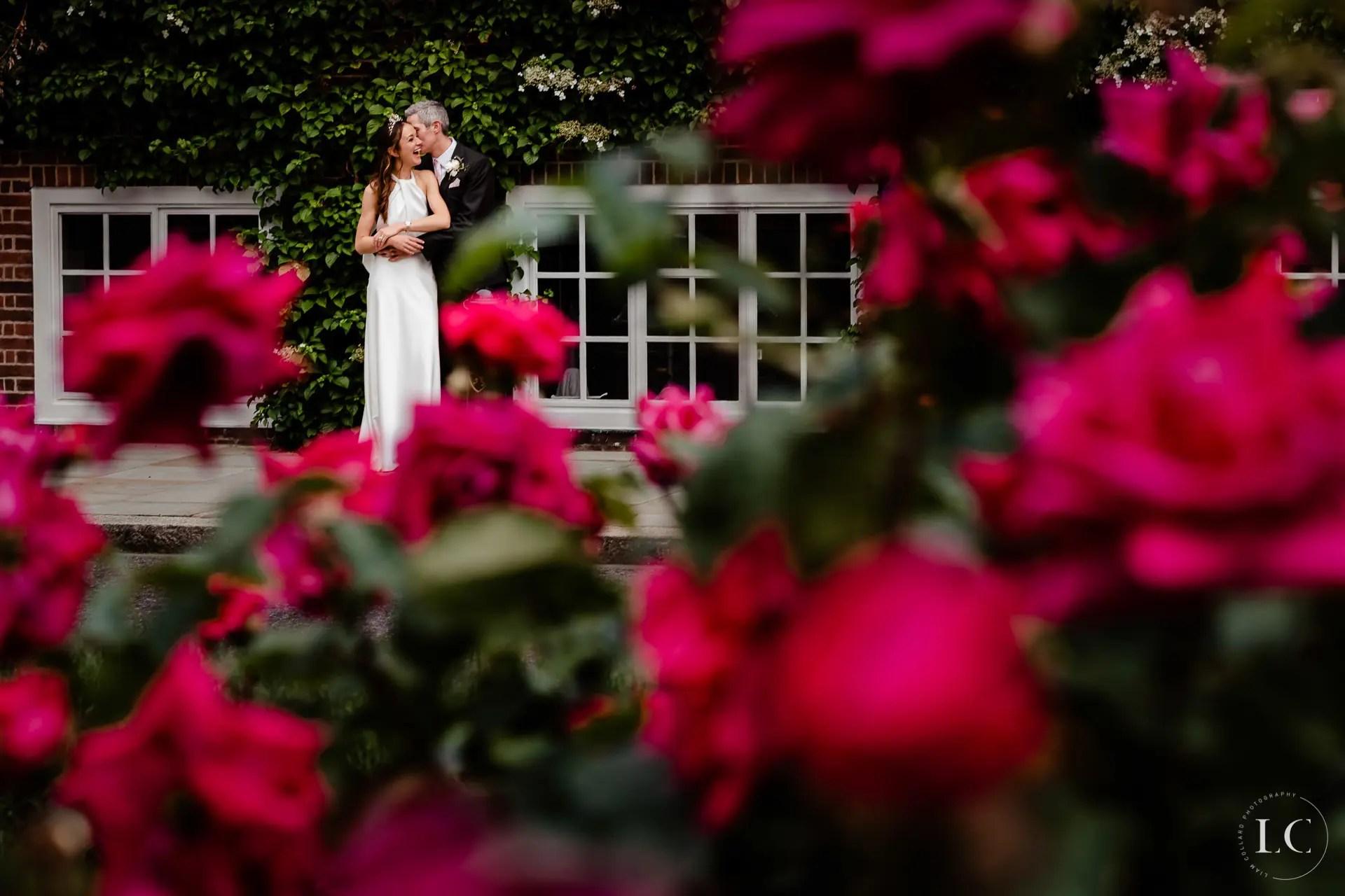 Bride and groom embracing among flowers