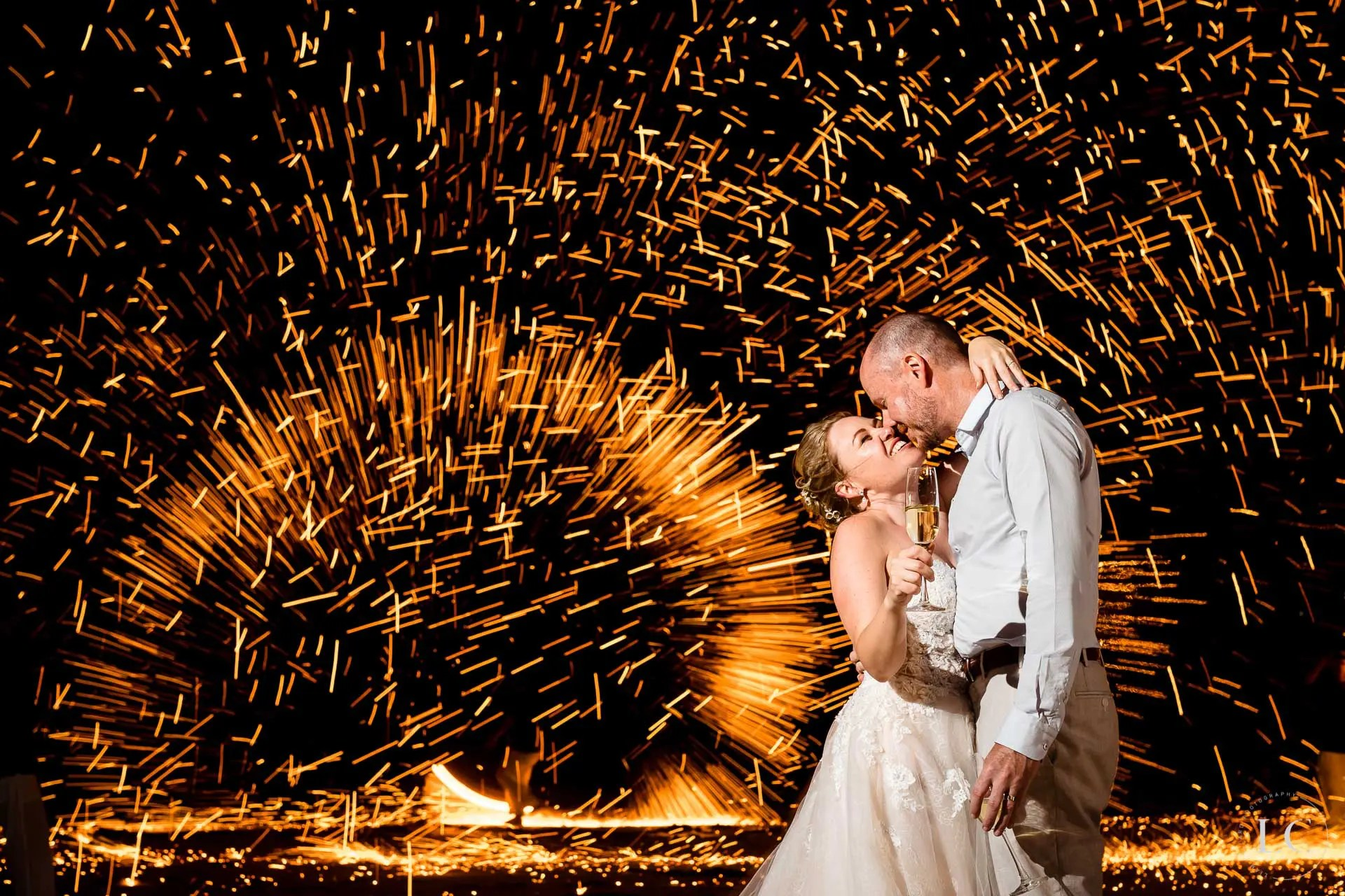 Bride and groom kissing and fireworks