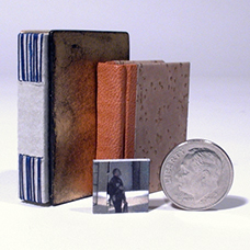 Jim Reid-Cunningham miniature bookbindings with coin for scale