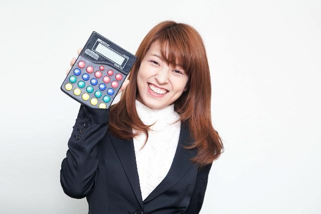 予算を計算する電卓を持った女性写真