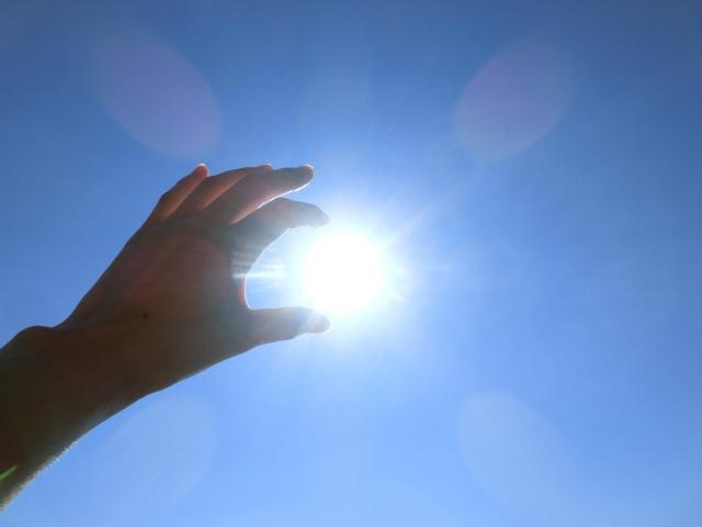 太陽に手を伸ばしているイメージ
