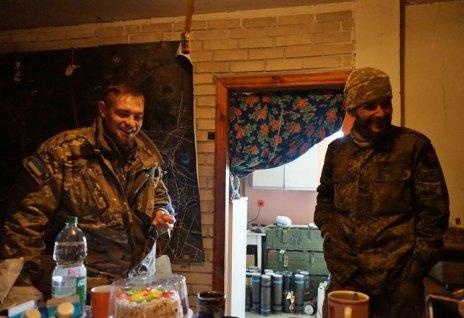 Due volontari all'interno della loro base improvvisata; casse di ammunizioni sono visibili sullo sfondo.