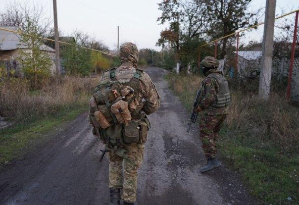 Volontari ucraini in pattugliamento in un villaggio abbandonato