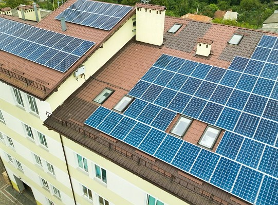 Aerial view of solar power plant with blue photovoltaic panels mounted of apartment building roof.