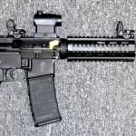Preowned Bushmaster QRC AR-15 Semi Auto Rifle, .223 / 5.56 NATO, 16″ Barrel, 30 Rounds, Collapsible Stock, Red Dot Sight, Flip-Up Iron Sights, Aluminum Carbine Length Quad Rail: $449
