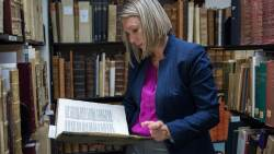 Polina Ilieva, Head Archivist reviewing a rare book from the Archives & Special Collections.