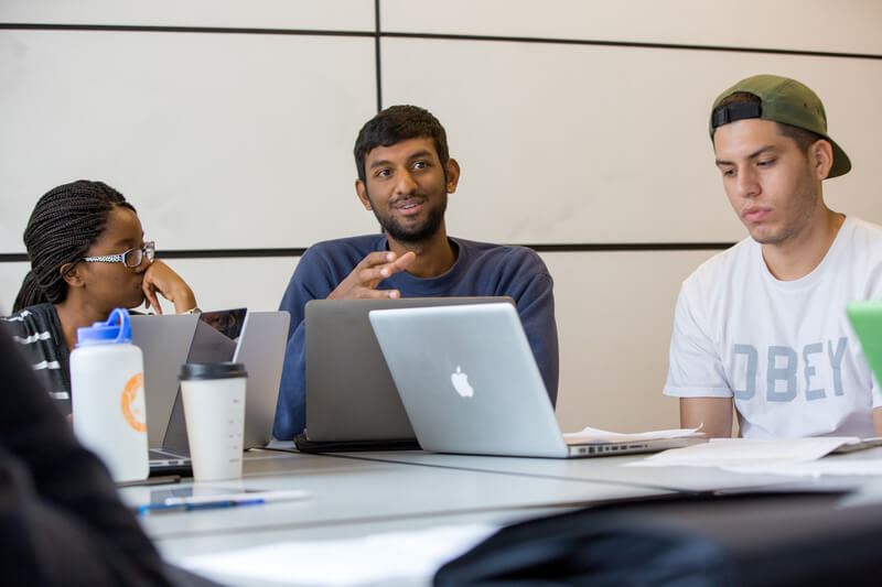 Students with laptops having discussion