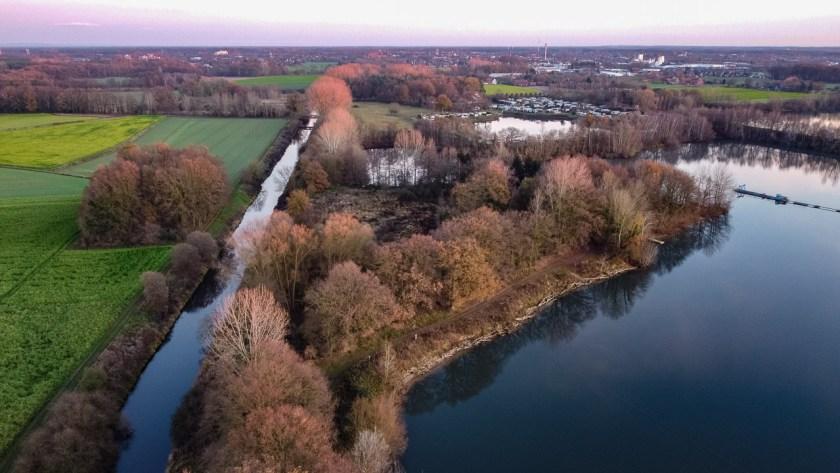 Die Baumkronen am Kottruper See und der Ems werden von der untergehenden Sonne angestrahlt