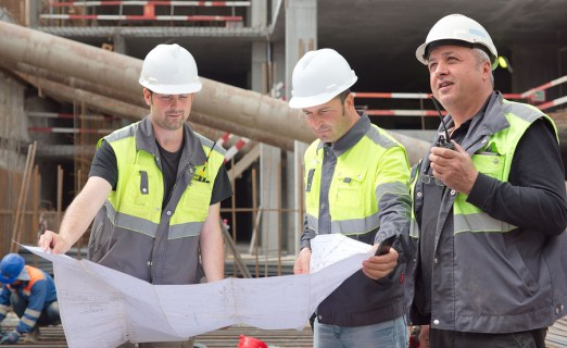 Two civil engineers and a senior foreman at construction site are inspecting ongoing construction works according to design drawings.