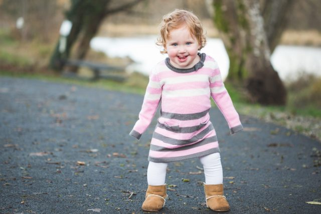 Two year old girl wearing pink and grey dress standing on asphalt walkway.